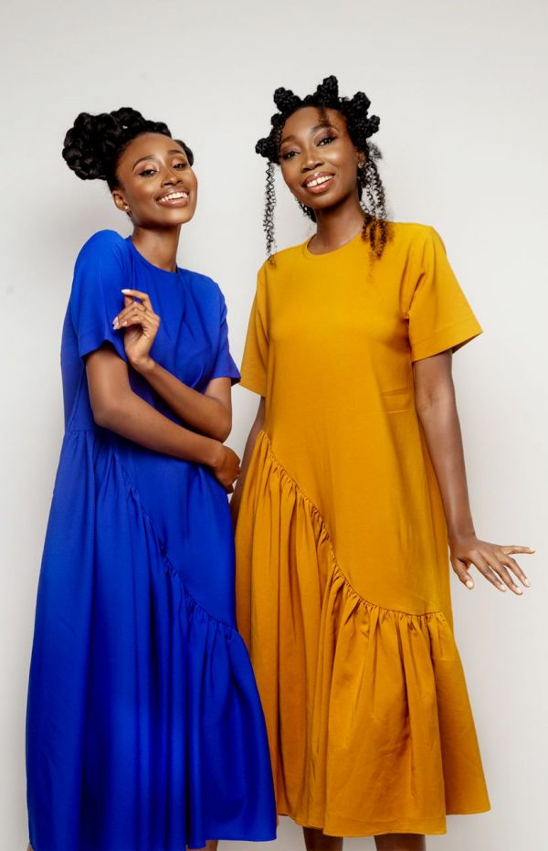 Two girls wearing blue and amber dresses
